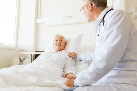 Foto de medicine, age, support, health care and people concept - doctor visiting and cheering senior woman lying in bed at hospital ward - Imagen libre de derechos