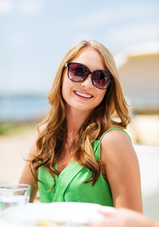 Foto de summer holidays and vacation - girl in shades in cafe on the beach - Imagen libre de derechos