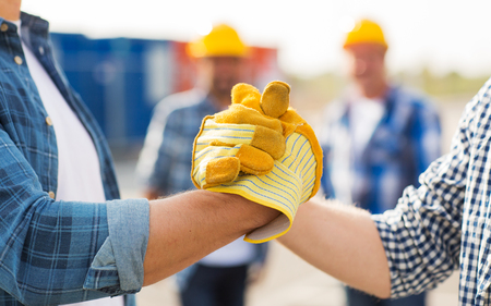 Foto per building, teamwork, partnership, gesture and people concept - close up of builders hands in gloves greeting each other with handshake on construction site - Immagine Royalty Free