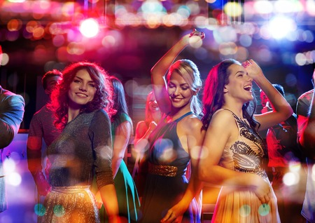 Photo pour party, holidays, celebration, nightlife and people concept - happy friends dancing in club with holidays lights - image libre de droit