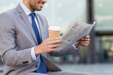 Photo for business, news, break and people and concept - close up of smiling businessman reading newspaper and drinking coffee from paper cup over office building - Royalty Free Image