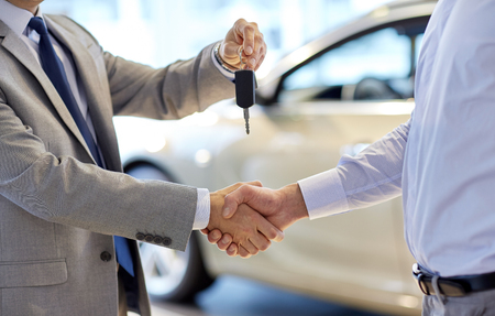 Foto de auto business, car sale, deal, gesture and people concept - close up of dealer giving key to new owner and shaking hands in auto show or salon - Imagen libre de derechos