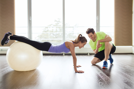 Foto de sport, fitness, lifestyle and people concept - smiling man and woman working out with exercise ball in gym - Imagen libre de derechos