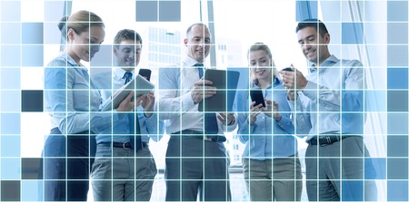 Photo pour business, teamwork, people and technology concept - business team with tablet pc and smartphones meeting in office over blue squared grid background - image libre de droit