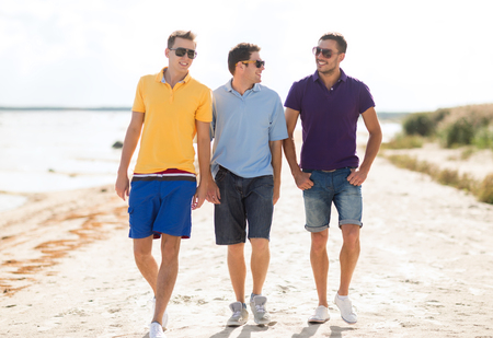 Photo for friendship, summer vacation, holidays and people concept - group of smiling male friends in sunglasses walking along beach - Royalty Free Image