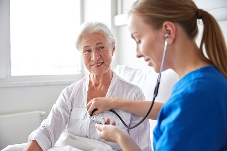 Foto de medicine, age, support, health care and people concept - doctor or nurse with stethoscope visiting senior woman and checking her heartbeat at hospital ward - Imagen libre de derechos