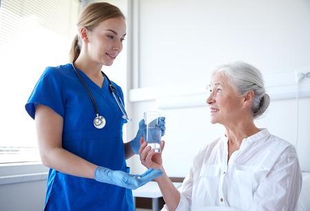 Foto de medicine, age, health care and people concept - nurse giving medication and glass of water to senior woman at hospital ward - Imagen libre de derechos