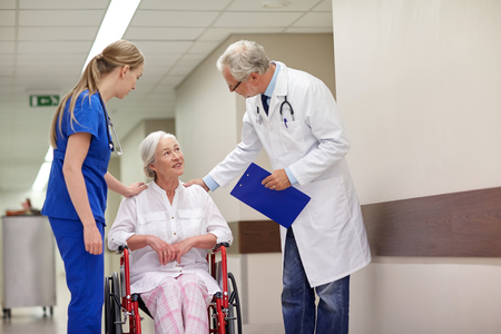 Photo for medicine, age, health care and people concept - doctor, nurse and senior woman patient in wheelchair at hospital corridor - Royalty Free Image
