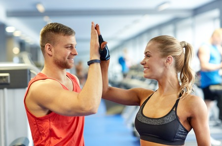 Photo for sport, fitness, lifestyle, gesture and people concept - smiling man and woman doing high five in gym - Royalty Free Image