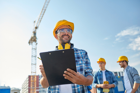 Photo for business, building, paperwork and people concept - happy builder in hardhat with clipboard and pencil over group of builders at construction site - Royalty Free Image