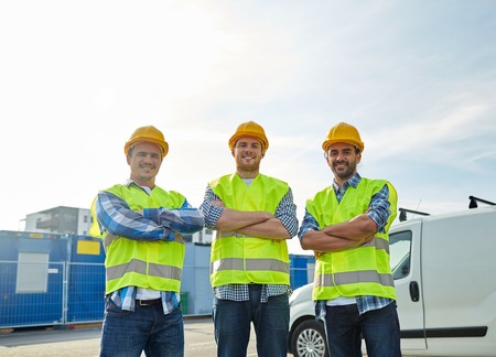 Foto de industry, building, construction and people concept - happy male builders in high visible vests outdoors - Imagen libre de derechos