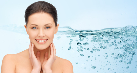 smiling young woman with bare shoulders touching her face over water splash on blue background