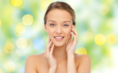 beauty, people and health concept - smiling young woman with bare shoulders touching her face over green lights background