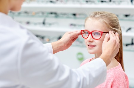 Foto de health care, people, eyesight and vision concept - optician putting glasses to little girl eyes at optics store - Imagen libre de derechos