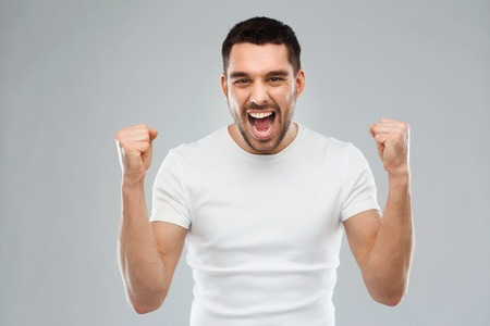 emotion, success, gesture and people concept - young man celebrating victory over gray background