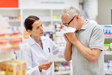 Foto de medicine, pharmaceutics, health care and people concept - pharmacist and sick senior man with flu blowing nose at pharmacy - Imagen libre de derechos