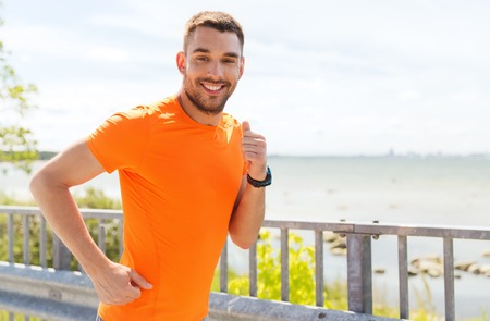 Foto de fitness, sport, people, technology and healthy lifestyle concept - smiling young man with heart rate watch running at summer seaside - Imagen libre de derechos