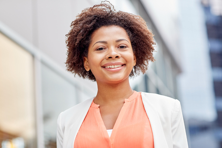 Photo pour business and people concept - young smiling african american businesswoman in city - image libre de droit
