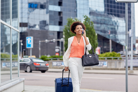 Foto de travel, business trip, people and technology concept - happy young african american woman with travel bag walking down city street and calling on smartphone - Imagen libre de derechos