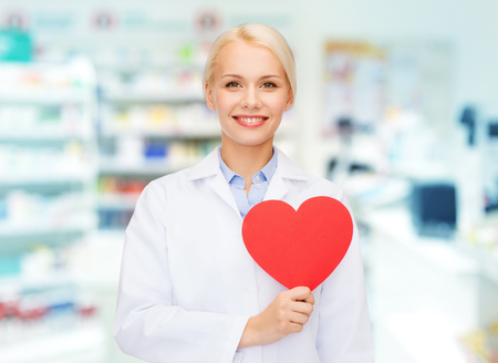 Foto de medicine, pharmacy, people, health care and pharmacology concept - happy young woman pharmacist holding red heart shape over drugstore background - Imagen libre de derechos