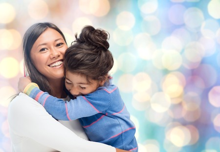 Foto de people, motherhood, family and adoption concept - happy mother and daughter hugging over blue holidays lights background - Imagen libre de derechos
