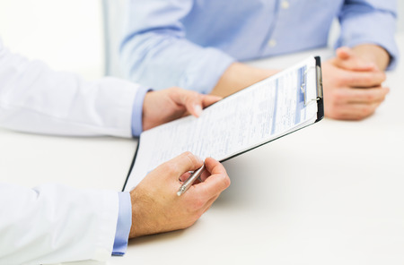 Photo pour medicine, health care, people and prostate cancer concept - close up of f male doctor and patient hands with clipboard - image libre de droit