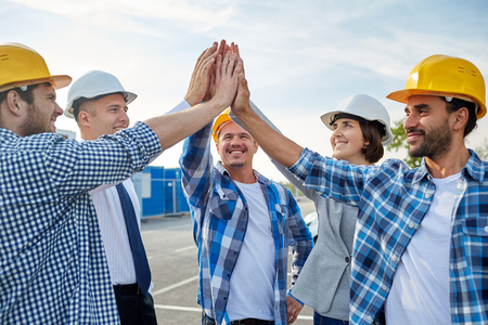 Foto de business, building, partnership, gesture and people concept - close up of smiling builders and architects in hardhats making high five outdoors - Imagen libre de derechos