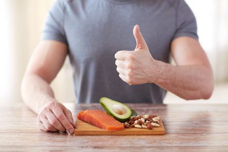 Photo for healthy eating, diet, gesture and people concept - close up of male hands showing thumbs up with food rich in protein on cutting board on table - Royalty Free Image