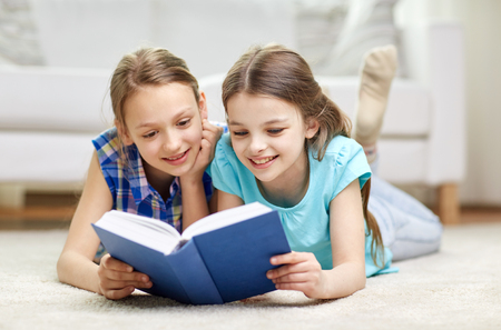 Photo pour people, children, friends, literature and friendship concept - two happy girls lying on floor and reading book at home - image libre de droit