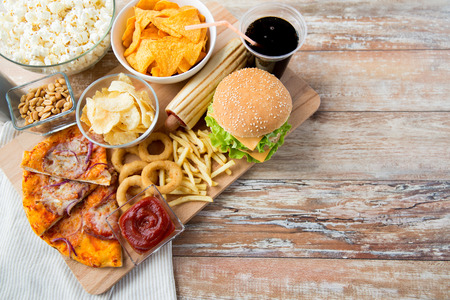 Photo pour fast food and unhealthy eating concept - close up of fast food snacks and coca cola drink on wooden table - image libre de droit