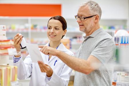 Foto de medicine, pharmaceutics, health care and people concept - happy pharmacist and senior man customer with drug and prescription at drugstore - Imagen libre de derechos