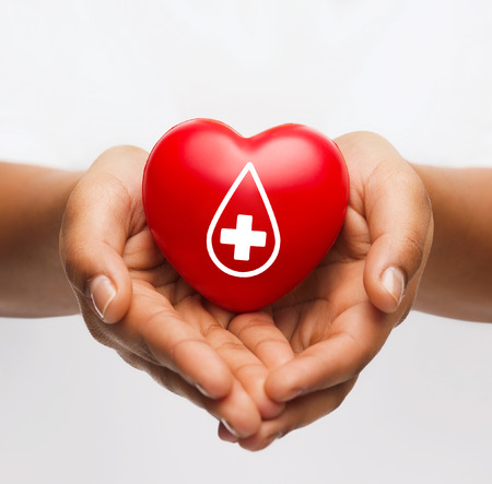 Foto de healthcare, medicine and blood donation concept - african american female hands holding red heart with donor sign - Imagen libre de derechos