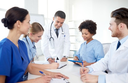 Photo for medical education, health care, people and medicine concept - group of happy doctors or interns with mentor meeting and taking notes at hospital - Royalty Free Image