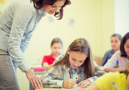 Foto de education, elementary school, learning and people concept - teacher helping school girl writing test in classroom - Imagen libre de derechos