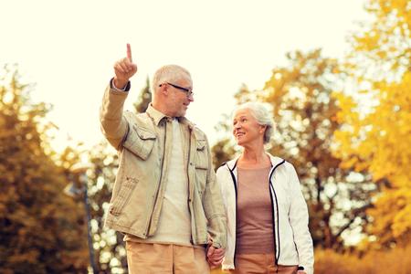 Foto de family, age, tourism, travel and people concept - senior couple pointing finger and walking in park - Imagen libre de derechos