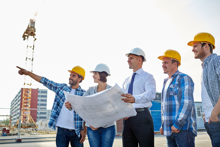 Photo pour group of builders and architects in hardhats with blueprint on construction site - image libre de droit