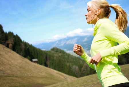 Foto de fitness, sport, people, technology and healthy lifestyle concept - happy young woman with earphones jogging or running  over mountains and blue sky background - Imagen libre de derechos