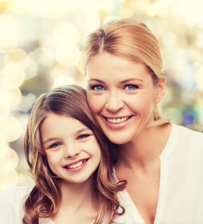 family, childhood, happiness and people - smiling mother and little girl over lights background