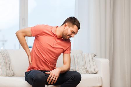 Foto de people, healthcare and problem concept - unhappy man suffering from pain in back or reins at home - Imagen libre de derechos