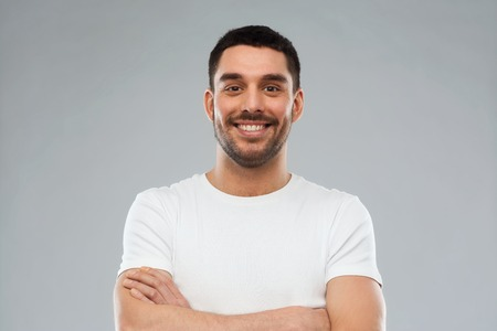 Foto de emotion and people concept - happy smiling young man with crossed arms over gray background - Imagen libre de derechos