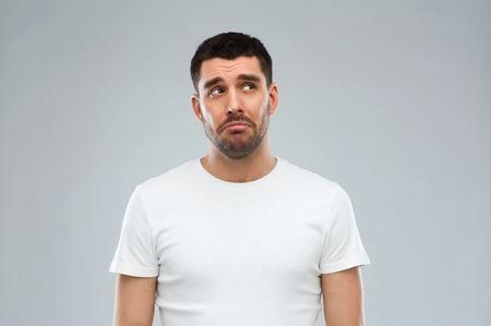 Foto de emotion, sadness and people concept - unhappy young man over gray background - Imagen libre de derechos