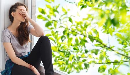 Foto de people, emotion and teens concept - sad unhappy pretty teenage girl sitting on windowsill over summer tree brunch background - Imagen libre de derechos
