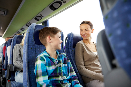 Foto de travel, tourism, family, technology and people concept - happy mother and son riding in travel bus - Imagen libre de derechos
