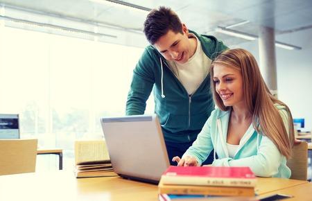 Foto de people, education, technology and school concept - happy students with laptop computer networking in library - Imagen libre de derechos
