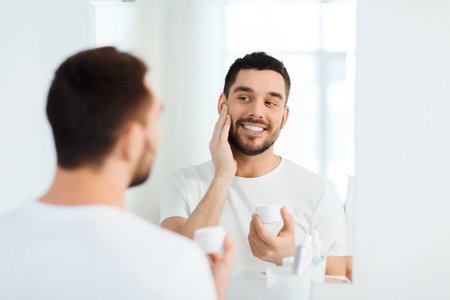 Photo pour beauty, skin care and people concept - smiling young man applying cream to face and looking to mirror at home bathroom - image libre de droit