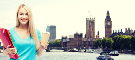 Foto de education, school, study abroad, drinks and people concept - smiling student girl with folders and cup of coffee over london city background - Imagen libre de derechos