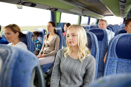 Photo pour transport, tourism, road trip and people concept - young woman with group of passengers or tourists in travel bus - image libre de droit
