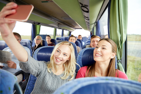 Photo pour transport, tourism, road trip and people concept - happy young women or friends in travel bus taking selfie by smartphone - image libre de droit
