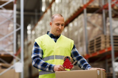Foto de logistic, delivery, shipment, people and export concept - happy man in safety vest packing box or parcel with scotch tape at warehouse or mail storage - Imagen libre de derechos