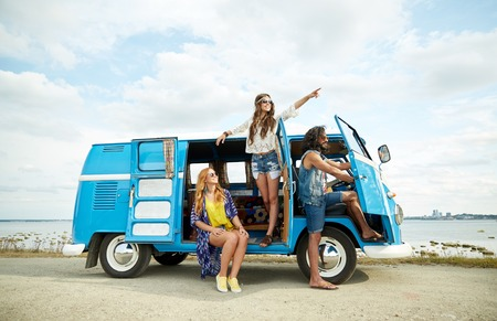 Photo for summer holidays, road trip, vacation, travel and people concept - smiling young hippie friends in minivan car on beach - Royalty Free Image